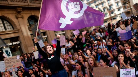 A woman waves a feminist flag as student protesters shout slogans during a demonstration marking International Women's Day in Barcelona on March 8, 2019.