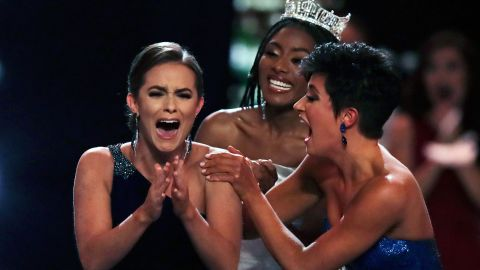 Camille Schrier, of Virginia, left, reacts after winning the Miss America competition while runner-up Miss Georgia Victoria Hill  2019 and Miss. America Nia Franklin congratulate her.
