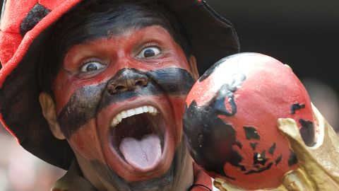 A Flamengo supporter cheers his team holding a fake Fifa World Cup before the start of the Brazilian Championship final match against Gremio, at the Maracana stadium on December 06, 2009 in Rio de Janeiro, Brazil. AFP PHOTO/Antonio Scorza (Photo credit should read ANTONIO SCORZA/AFP via Getty Images)