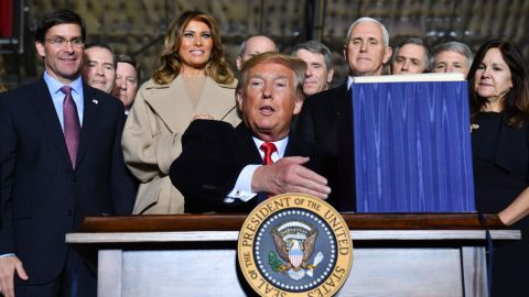"""Defense Secretary Mark Esper, First Lady Melania Trump, Vice President Mike Pence and Karen Pence watch US President Donald Trump sign the """"National Defense Authorization Act for FY2020"""" at Joint Base Andrews, Maryland on December 20, 2019. (Photo by Nicholas Kamm / AFP) (Photo by NICHOLAS KAMM/AFP via Getty Images)"""