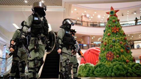 Riot police pass by Christmas decor in a shopping mall during a protest rally on Christmas Eve.
