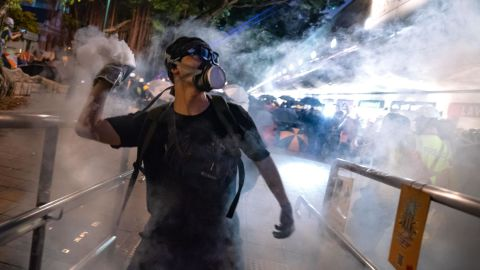 """HONG KONG, CHINA - AUGUST 11:  A protester throws back tear gas fired by riot police in the Cheung Sha Wan area on August 11, 2019 in Hong Kong, China. Pro-democracy protesters have continued rallies against a controversial extradition bill since June 9, when the city was plunged into crisis after waves of demonstrations and several violent clashes. While Hong Kong's Chief Executive Carrie Lam apologized for introducing the bill and declared it """"dead,"""" protests have continued to draw large crowds with demands for Lam's resignation and a complete withdrawal of the bill. (Photo by Billy H.C. Kwok/Getty Images)"""