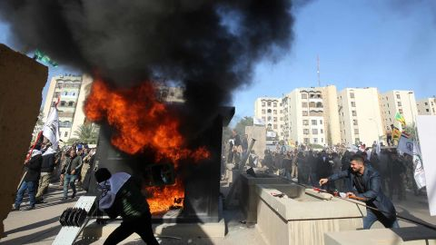 Iraqi protesters set a sentry box ablaze in front of the US embassy in Baghdad on Tuesday.