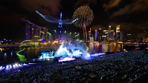 Drones form the shape of a crane in the sky as fireworks erupt at Singapore's Marina Bay.