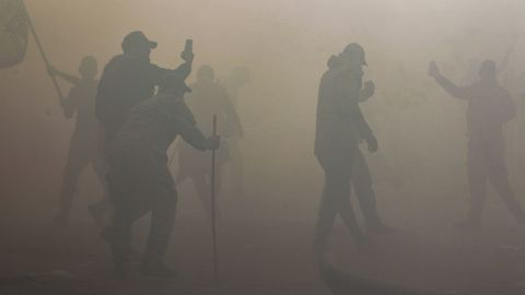 People are seen through thick tear gas after protesters breached the outer wall of the embassy.