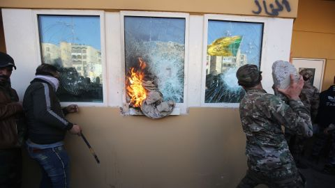 Protesters and militia fighters smash the bullet-proof glass of the embassy's windows with blocks of cement after breaching the outer wall.