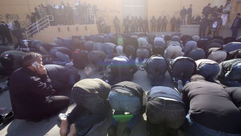 Iraqi security forces stand guard as protesters, including clerics, hold a prayer inside the walls of the embassy.