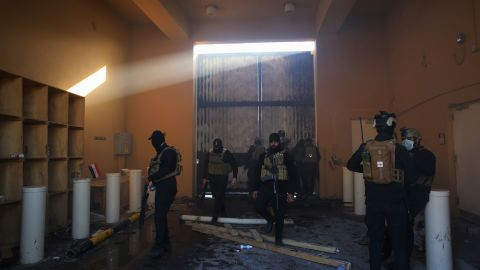 Iraqi security forces stand guard at the entrance of embassy.