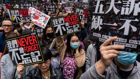Pro-democracy supporters hold placards as they take part in a New Year's Day rally on Wednesday, January 1 in Hong Kong.
