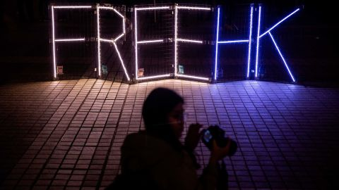 Protesters take photos of a 'Free HK' light display at a gathering in the Central district of Hong Kong on December 30.
