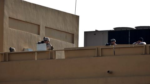 US Marines stand guard on the roof of the US Embassy while protesters demonstrate on Wednesday.