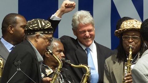 Clinton cheers a group of saxophone players at a rally in New York in July 2001. Harlem residents were welcoming Clinton, who was moving into his new post-presidential office.