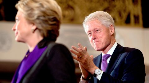 Clinton listens to his wife speak to supporters after her election defeat in 2016.