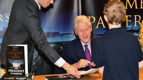 """In June 2018, Clinton signs copies of his novel """"The President Is Missing,"""" which he co-wrote with James Patterson."""