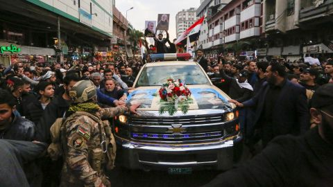 Mourners throng the car carrying the body of Iranian commander Qasem Soleimani during a funeral procession for Soleimani and Iraqi paramilitary leader Abu Mahdi al-Muhandis in Baghdad on January 4.