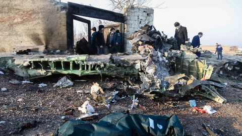 People stand near the wreckage after a Ukrainian plane carrying 176 passengers crashed near Imam Khomeini airport in Tehran on January 8, 2020. - All 176 people on board a Ukrainian passenger plane were killed when it crashed shortly after taking off from Tehran on January 8, Iranian state media reported. State news agency IRNA said 167 passengers and nine crew members were on board the aircraft operated by Ukraine International Airlines.