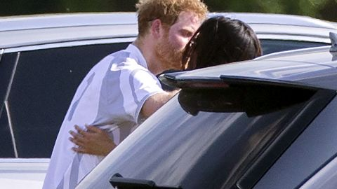 Harry and Meghan embrace at a polo match in May 2017.
