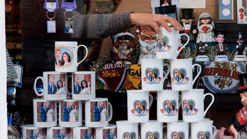 """A shop worker in Windsor, England, adjusts memorabilia celebrating the engagement of Harry and Meghan. Their engagement <a href=""""https://edition.cnn.com/2017/11/27/europe/prince-harry-meghan-markle/index.html"""" target=""""_blank"""">was announced</a> in November 2017."""