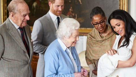Queen Elizabeth II looks at her new great-grandchild, Archie, in May 2019. Prince Philip is on the far left. Meghan's mother, Doria Ragland, is next to her at right.