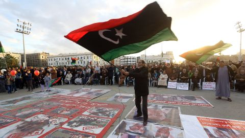 Demonstrators wave flags and step on posters of some world leaders as they take part in a rally against eastern Libyan strongman Khalifa Haftar, and in support of the UN-recognised government of national accord (GNA) in Martyrs' Square in the GNA-held capital Tripoli on January 10, 2020. (Photo by MAHMUD TURKIA/AFP via Getty Images)