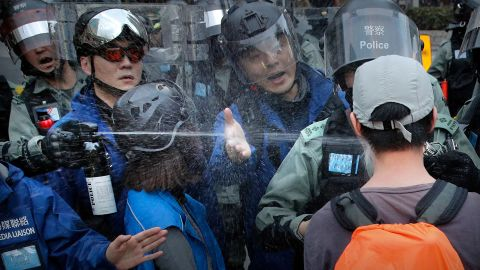 """A riot policeman sprays pepper spray at a man as they disperse a crowd during a demonstration against """"parallel traders"""" who buy goods in Hong Kong to resell in mainland China on Sunday, January 5."""