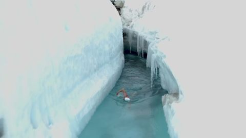man swims through glacier lake