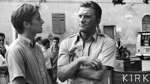 """Douglas appears with his son Michael on the set of the film """"Cast a Giant Shadow"""" in Rome in the mid-'60s. Michael Douglas had a small uncredited role in his dad's movie. He would go on to become a major film star himself in the 1980s and '90s."""