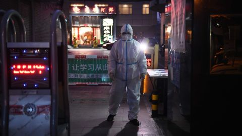 A security guard wears protective clothing as a preventive measure against the COVID-19 coronavirus as he stands at the entrance of a restaurant in Beijing on February 25, 2020. - China on February 25 reported another 71 deaths from the novel coronavirus, the lowest daily number of fatalities in over two weeks, which raised the toll to 2,663. (Photo by Greg Baker/AFP/Getty Images)