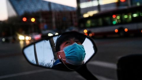 BEIJING, CHINA - FEBRUARY 22: A Chinese man is seen in the side mirror of his scooter as he wears a protective mask while waiting at a red light on February 22, 2020 in Beijing, China. The number of cases of the deadly new coronavirus COVID-19 being treated in China was more than 55000 in mainland China Saturday, in what the World Health Organization (WHO) has declared a global public health emergency. China continued to lock down the city of Wuhan in an effort to contain the spread of the pneumonia-like disease which medicals experts have confirmed can be passed from human to human. In an unprecedented move, Chinese authorities have maintained and in some cases tightened the travel restrictions on the city which is the epicentre of the virus and also in municipalities in other parts of the country affecting tens of millions of people. The number of those who have died from the virus in China climbed to over 2348 on Saturday mostly in Hubei province, and cases have been reported in other countries including the United States, Canada, Australia, Japan, South Korea, India, the United Kingdom, Germany, France and several others. The World Health Organization has warned all governments to be on alert and screening has been stepped up at airports around the world. Some countries, including the United States, have put restrictions on Chinese travelers entering and advised their citizens against travel to China. (Photo by Kevin Frayer/Getty Images)