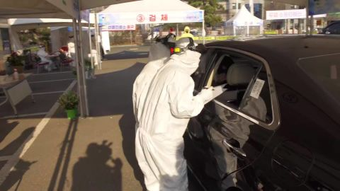 Health officials test patients through a car window at the drive-through site.