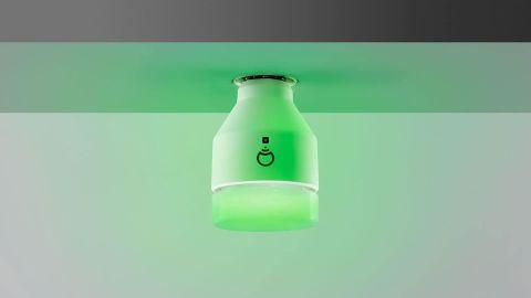 A LIFX smart bulb glowing green.