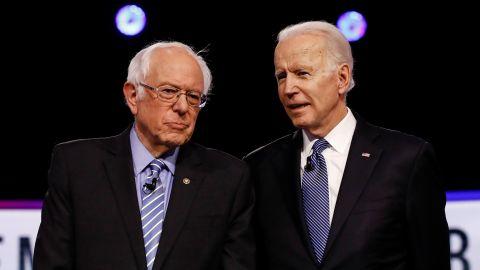 Sanders and former Vice President Joe Biden talk before a Democratic debate in Charleston, South Carolina, in February 2020.