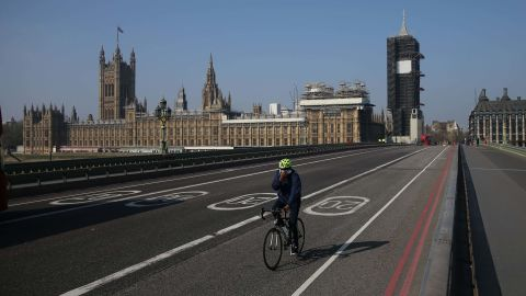 A cyclist crosses a near-empty Westminster Bridge with the Houses of Parliament in the background in central London on April 9, 2020. - British Prime Minister Boris Johnson on Thursday began a fourth day in intensive care