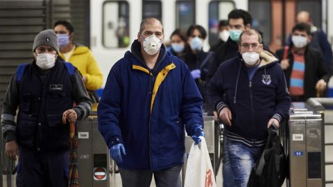 Spanish workers wear masks leaving the subway on April 13, in Madrid.