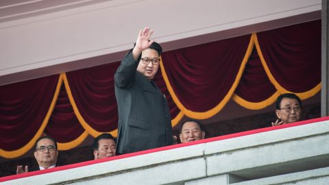 Kim waves as he walks past top-ranking party officials during a parade in Pyongyang in May 2016.