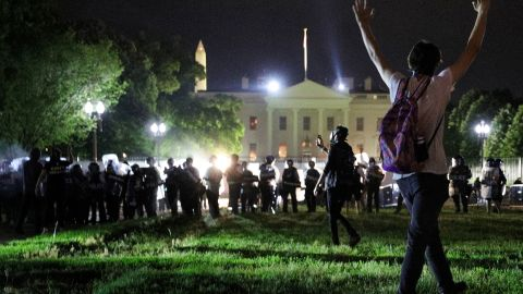 A protester holds his hands up as police officers enter Lafayette Park during a demonstration against the death in Minneapolis police custody of African-American man George Floyd, as the officers keep demonstrators away from the White House during a protest in Washington, U.S. May 30, 2020. REUTERS/Tom Brenner
