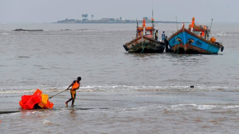 A fisherman pulls a handcart filled with crates inland ahead of a cyclonic storm in the north western coast of Mumbai on June 2.