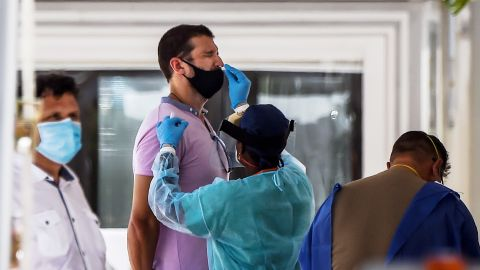A healthcare worker takes a sample from a man at a COVID-19 testing site in Miami Beach, Florida on Wednesday, June 24, 2020.  Photo by Chandan Khanna/AFP/Getty Images