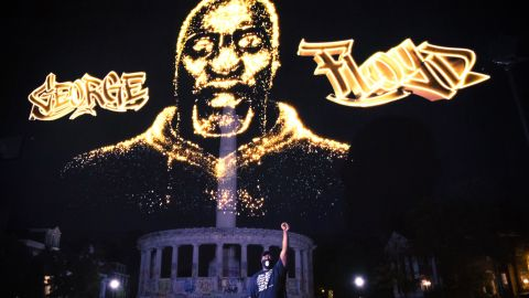 Rdoney Floyd stands in front of a hologram honoring his brother as it is projected over the Robert E. Lee statue in Richmond, Virginia, during a private event on July 27.  CNN obscured portions graffiti on the statue that contained profanity.