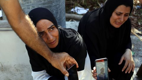 A woman and her sister-in-law show a photo of a missing man on August 7, 2020. Many people were reported missing after the explosion.