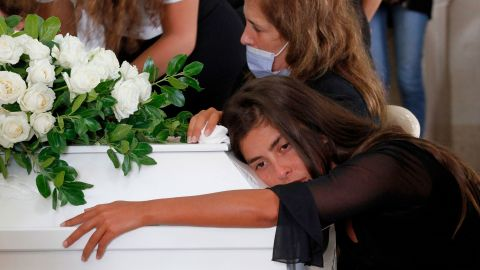 Christelle Helou hugs the coffin of her cousin Nicole in Sarba, Lebanon, on August 6, 2020.