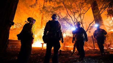 Firefighters make a stand in the backyard of a home in front of the advancing CZU August Lightning Complex Fire on Friday, August 21, in Boulder Creek, California.
