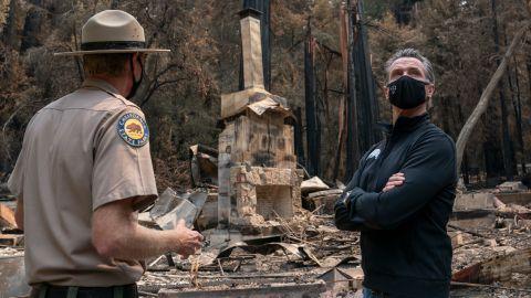 California Gov. Gavin Newsom, right, listens as Santa Cruz State Park Superintendent Chris Spohrer talks about the fire damage to the Big Basin Redwoods State Park.