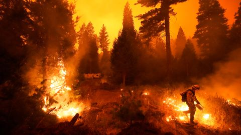 A firefighter sets a controlled burn with a drip torch while fighting the Creek Fire in Shaver Lake.