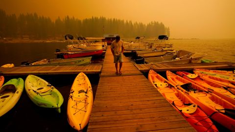 A business owner in Shaver Lake walks next to kayaks he rents as smoke from the Creek Fire fills the sky on September 6.