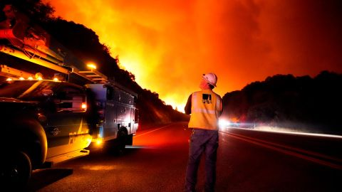 A Pacific Gas and Electric worker looks up at the advancing Creek Fire near Alder Springs, California, on September 8.