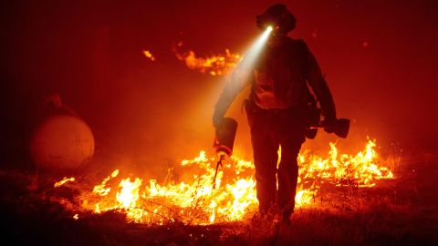 Firefighters cut defensive lines and light backfires to protect structures in Butte County, California, on September 9.