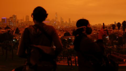 """Visitors of San Francisco's Dolores Park are seen under an orange sky <a href=""""https://www.cnn.com/2020/09/09/weather/california-orange-skies-wildfires-photos-trnd/index.html"""" target=""""_blank"""">darkened by smoke</a> on September 9."""
