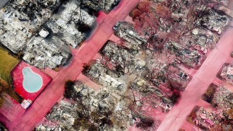 In this aerial photo taken with a drone, red fire retardant sits on leveled homes in Talent, Oregon, on September 15.