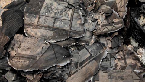 A charred yearbook lies in the debris as Fred Skaff and his son Thomas clean up their home in Phoenix, Oregon, on September 16.